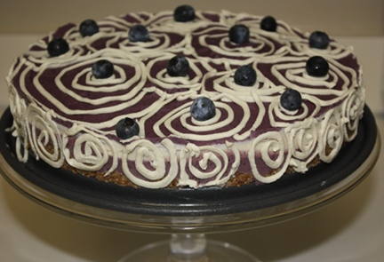 Raw vegan blueberry cake with fresh blueberries and a date nut crust.