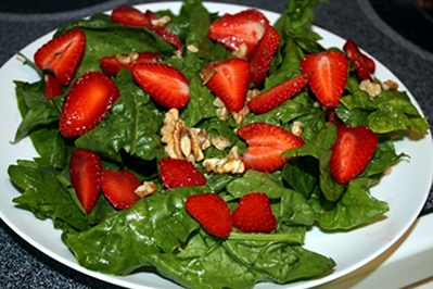 Leafy green salad full of spinach, walnuts, and strawberries is a perfect way to get plenty of plant protein and vegan calcium.