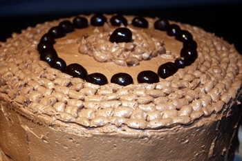 Mocha Cake frosted with vegan chocolate frosting flavored with coffee and covered in chocolate espresso beans.