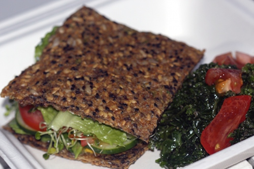 The Raw and Juicy veggie sandwich is made with flax bread, loaded with vegetables, and served with a kale salad.