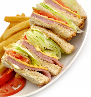 A typical Western club sandwich is on enriched white bread, is loaded with meat, mayonnaise and cheese, and has a few limp vegetables.