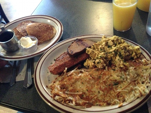 The Lumberjack at Wayward Vegan Cafe is loaded with tofu scramble, homefries, fake ham, tempeh bacon, and three pancakes.