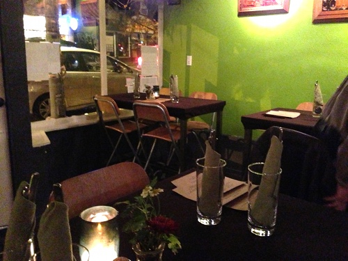 The view from inside Sutra Restaurant in Seattle, counter height tables and simple dinnerware.
