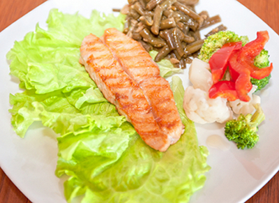 A typical meal for a health conscious Westerner-- a huge piece of farmed salmon with a tiny portion of overcooked vegetables.