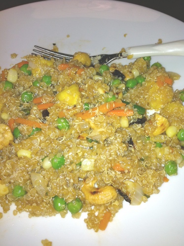 Quinoa stir fried with pineapple, carrots, and green peas in a tropical twist.