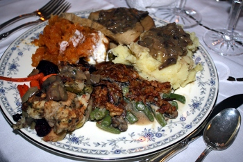 A plate piled high with vegan Thanksgiving recipes, including spiced sweet potatoes with Dandies, Brussel's sprouts, and garlic mashed potatoes.